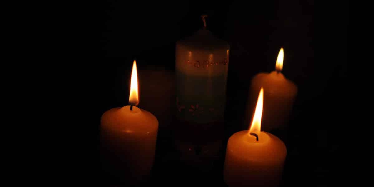 Julkranz mit drei brennenden Kerzen