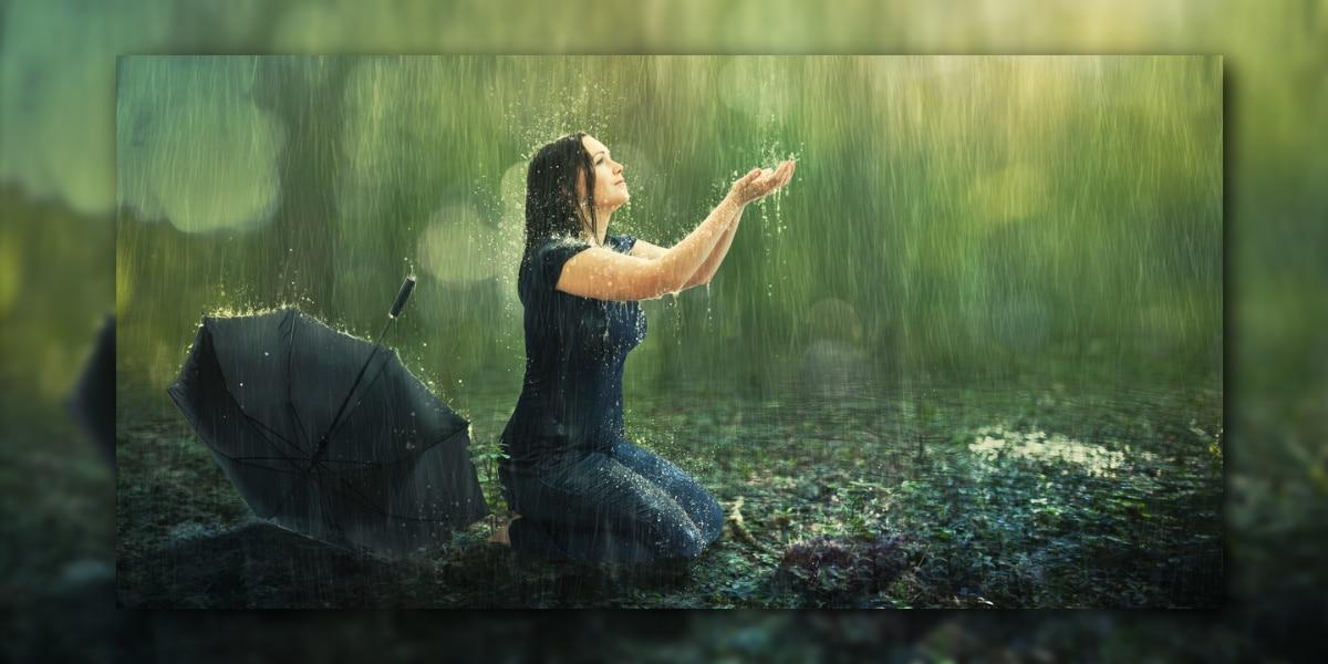Frau kniet im Regen